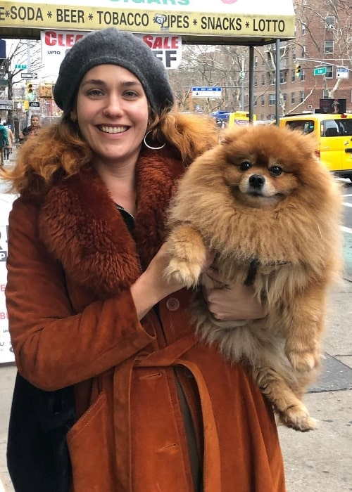Lola Kirke posing with a furry dog in December 2018