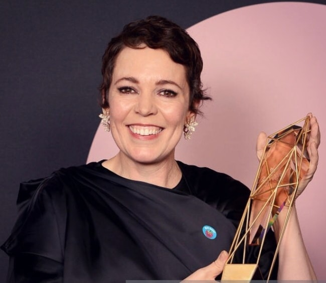 Olivia Colman posing with a trophy