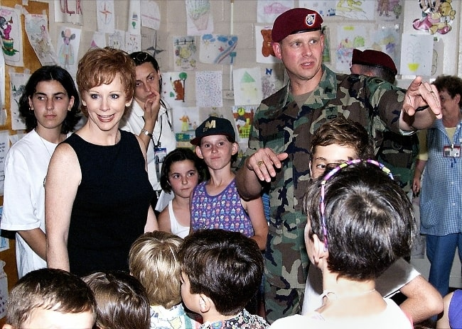 Reba McEntire (in a black dress) with Kosovo refugees in June 1999