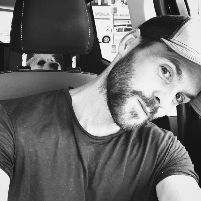 Tom Riley in a black-and-white car-selfie with his dog in the background in September 2018