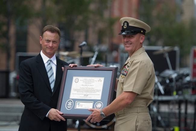 Gary Sinise being honored as an honorary chief petty officer by Fleet Master Chief Michael Stevens during a ceremony at the Navy Memorial and Naval Heritage Center in August 2012