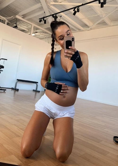 Kayla Itsines showing her baby bump in a gym mirror selfie in January 2019