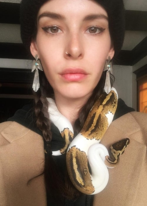 Carly Foulkes pictured with a snake wrapped around her neck in March 2019