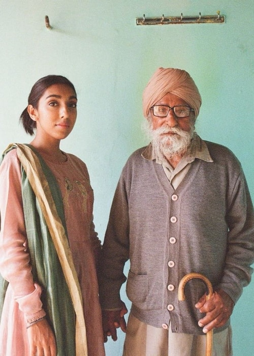 Rupi Kaur posing with her last living grandparent, her maternal grandfather, in her homeland of Punjab, India in April 2018