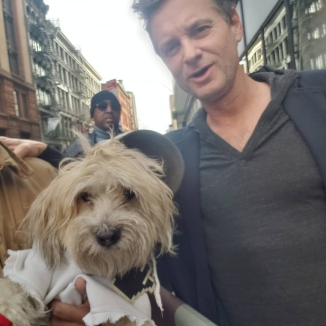 Shea Whigham posing with Coqui /Shaggy, the Maltipoo, in February 2019