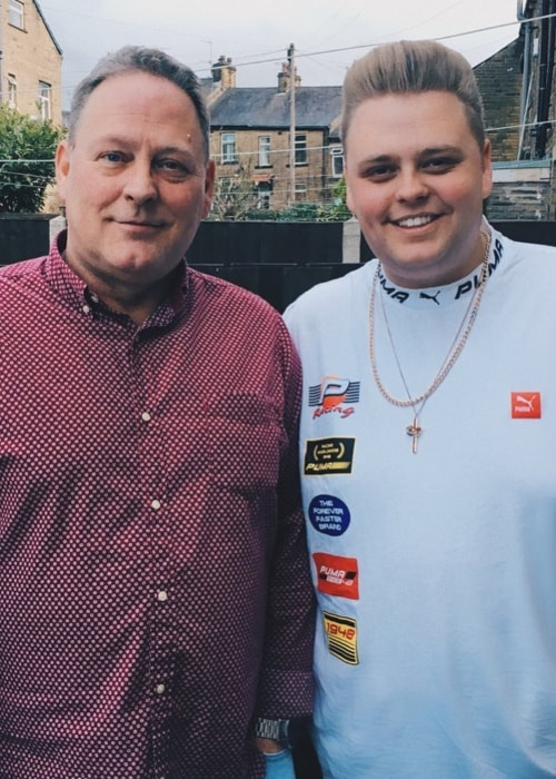Nick Crompton sporting a white outfit while posing with his father in December 2017