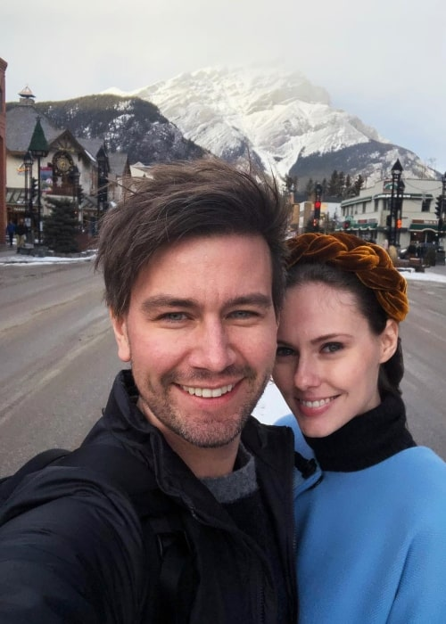 Torrance Coombs as seen while taking a selfie, with a backdrop of snow covered mountains, with Alyssa Campanella in Banff, Alberta in December 2018