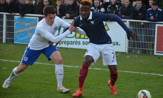 Ben Chilwell (Left) and Maxwel Cornet wrestling for the ball during the qualification match between France and England for the 2015 European Under-19 Football Championship at Louis Villemer Stadium in Saint-Lô, France in March 2015
