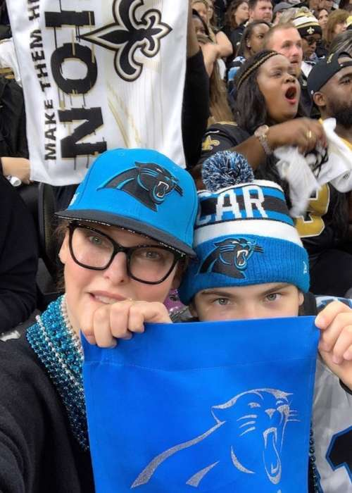 Linda brandishing a Carolina Panthers flag with her son Augustin James during their match against New Orleans Saints in December 2018