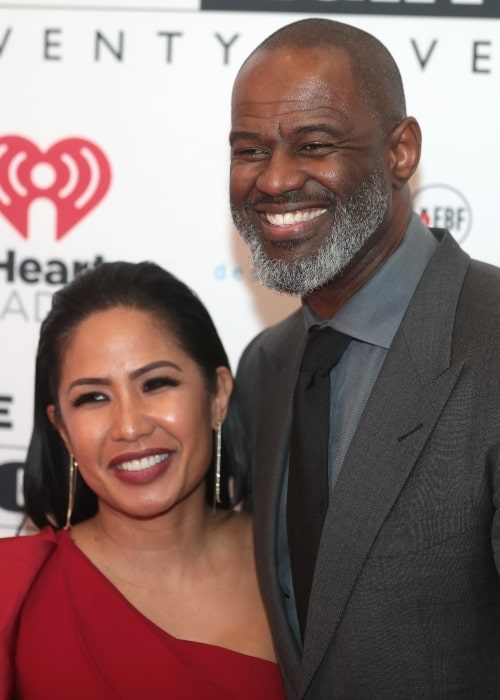 Brian McKnight as seen while posing for a picture with his wife on the red carpet at Celebrity Fight Night XXV at the JW Marriott Desert Ridge Resort & Spa in Phoenix, Arizona in March 2019