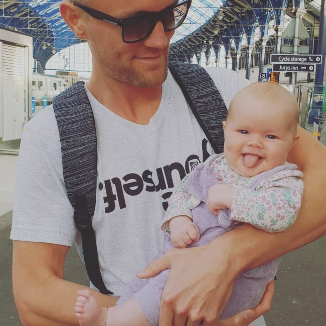 Karma Oak as seen with her father, Darren Fizz, and sticking out her tongue while looking at the camera and posing for a picture before embarking on her first ever plane ride in October 2018