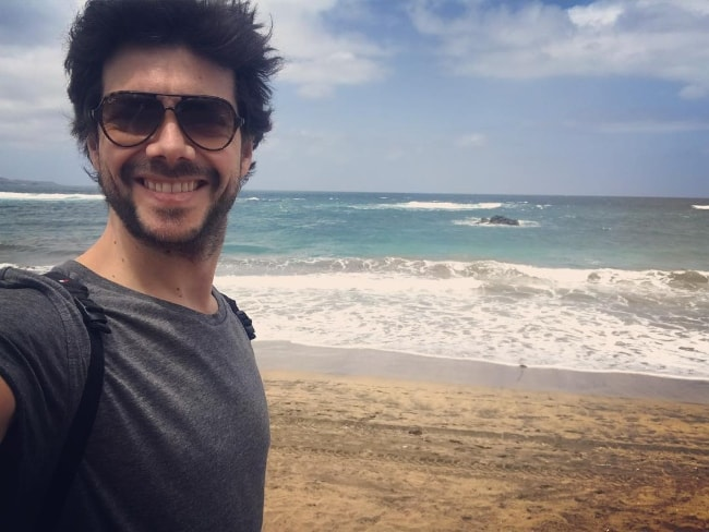 Álvaro Morte as seen while taking a selfie by a beach in April 2018