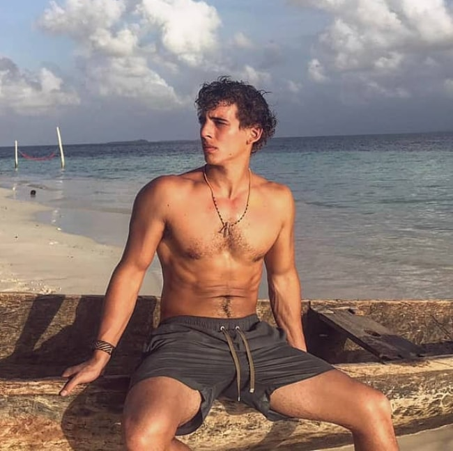 Miguel Herrán as seen shirtless while posing for a picture by a beach with a beautiful backdrop in April 2019