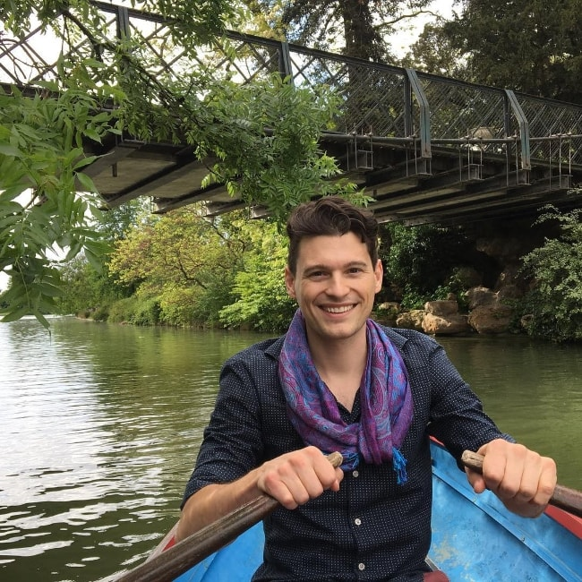 Bryan Dechart smiling for a picture while on a rowboat in Paris, France along with his beloved lady, Amelia Rose Blaire, in May 2017