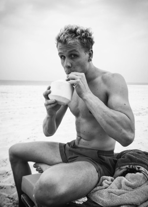 Josh Dylan as seen in an stunning shirtless black-and-white picture while drinking coconut water in March 2019