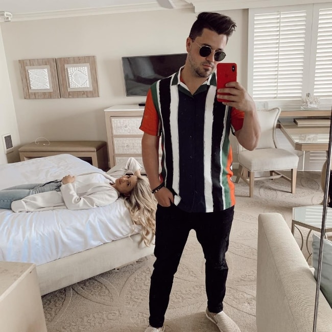 Kyler Fisher as seen while taking a mirror selfie with wife Madison Nicole Fisher lying on the bed in the background in Laguna Beach, Orange County, California, United States in April 2019