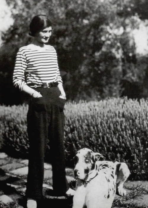 Coco Chanel as seen while standing beside a dog in 1928