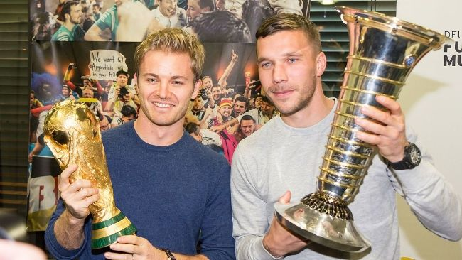 Lukas holding the F1 World Championship trophy and Formula One race driver Nico Rosberg posing with the FIFA World Cup trophy in 2016