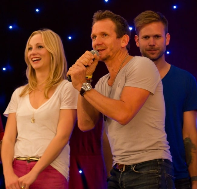 Sebastian Roché as seen while speaking during an event with Candice Accola on his side and Matt Davis behind him in June 2013