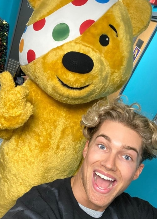 AJ Pritchard as seen in a selfie with a teddy bear mascot costume posing at the back of him in November 2019