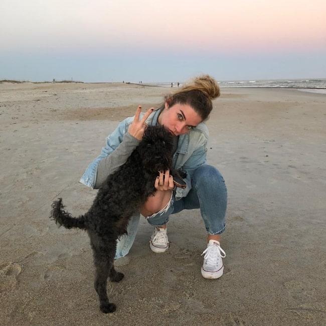 Annie Murphy as seen while posing for a picture with a stunning backdrop alongside her adoptive dog at Wrightsville Beach in New Hanover County, North Carolina, United States in February 2018