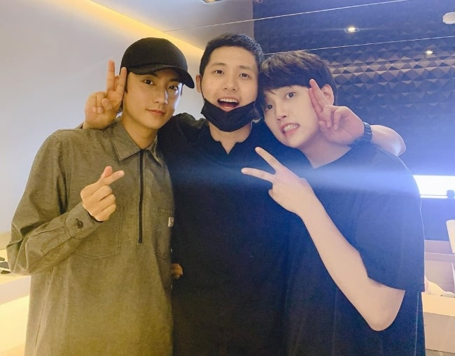 CNU as seen while posing for a picture along with his fellow 'B1A4' artists, Gongchan (Left) and Sandeul (Right), in May 2019