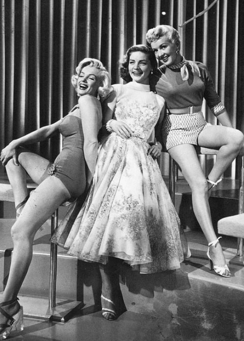 From Left to Right - Marilyn Monroe, Lauren Bacall, and Betty Grable as seen while smiling for a picture