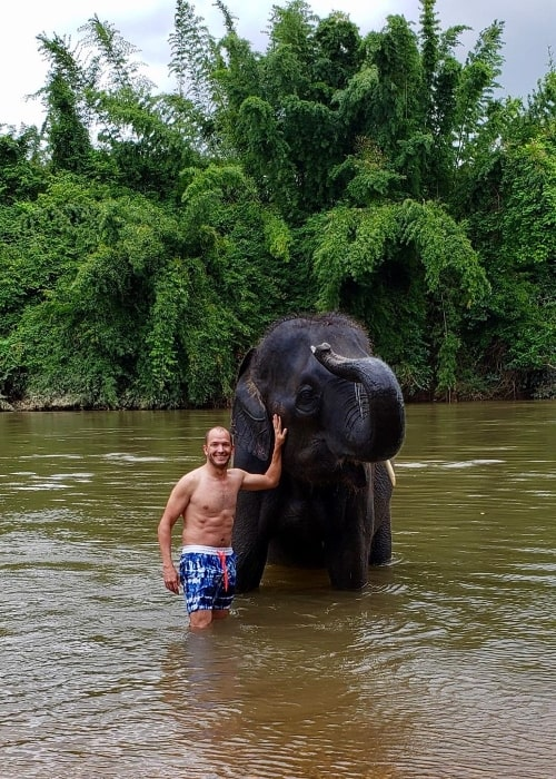 Jase Bennett as seen while posing for a picture alongside an elephant at Erawan National Park in Thailand in August 2019