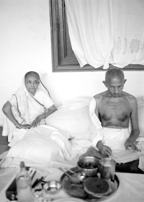 Mahatma Gandhi as seen in a picture with his wife Kasturbai Gandhi while reading
