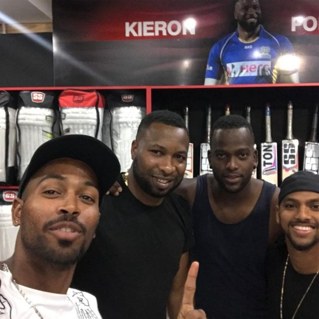 Kieron posing with fellow players Hardik Pandya, Kevon Cooper, and Nicholas Pooran in June 2017