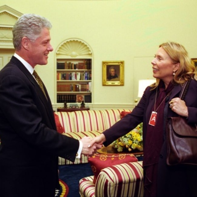 Joni Mitchell as seen in a picture taken while shaking the hand of the 42nd President of the United States Bil Clinton in the Oval Office on May 11, 1998