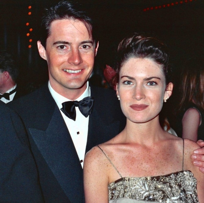 Lara Flynn Boyle as seen while smiling for the camera along with Kyle MacLachlan at the 42nd Emmy Awards - Governor's Ball in September 1990