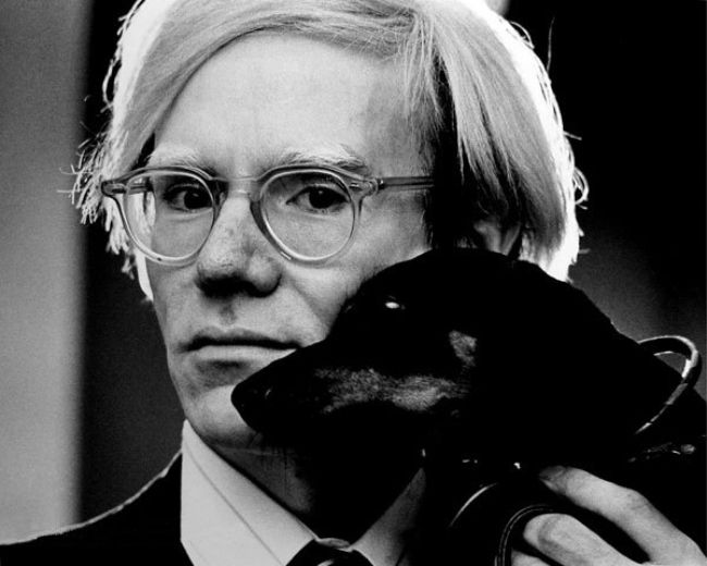 Andy Warhol posing with his pet dog Archie in 1973