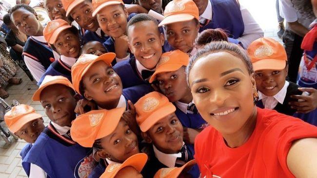 DJ Zinhle taking a selfie with school kids in February 2019