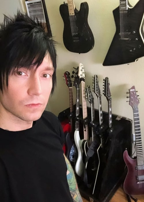Jake Pitts taking a selfie with his guitar collection in the background in November 2019