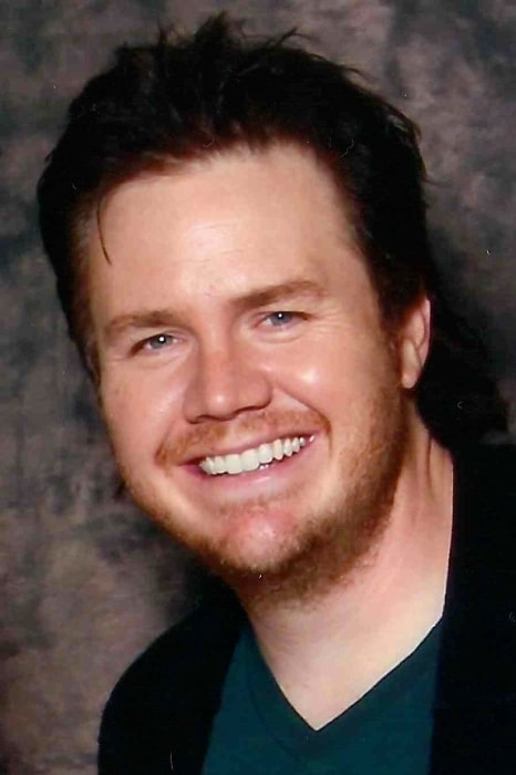 Josh McDermitt as seen while smiling in a picture at Walker Stalker Convention 2014