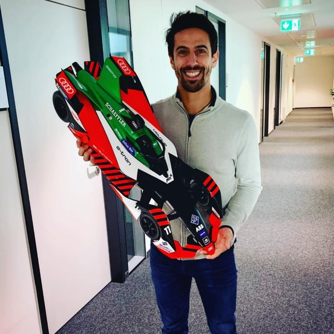 Lucas di Grassi with a miniature 3D-printed Formula E racecar, as seen in November 2019