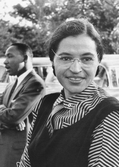 Rosa Parks as seen while smiling in a picture with Dr. Martin Luther King Jr. in the background in 1955