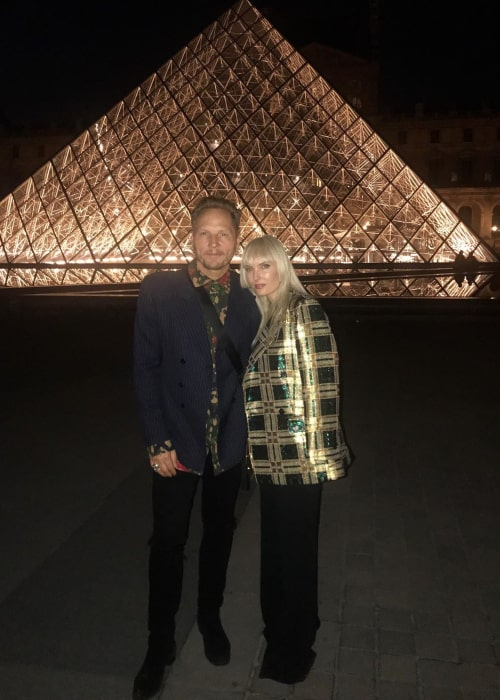 "Matt Sorum and Adriane ""Ace"" Harper, posing in front of The Louvre in Paris in June 2019"