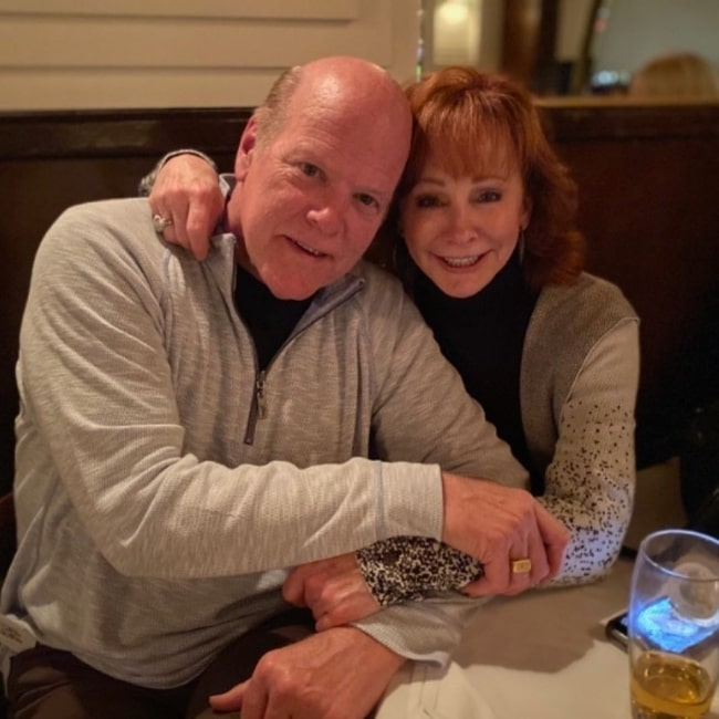 Rex Linn and Reba McEntire smiling for a picture while enjoying a dinner in January 2020
