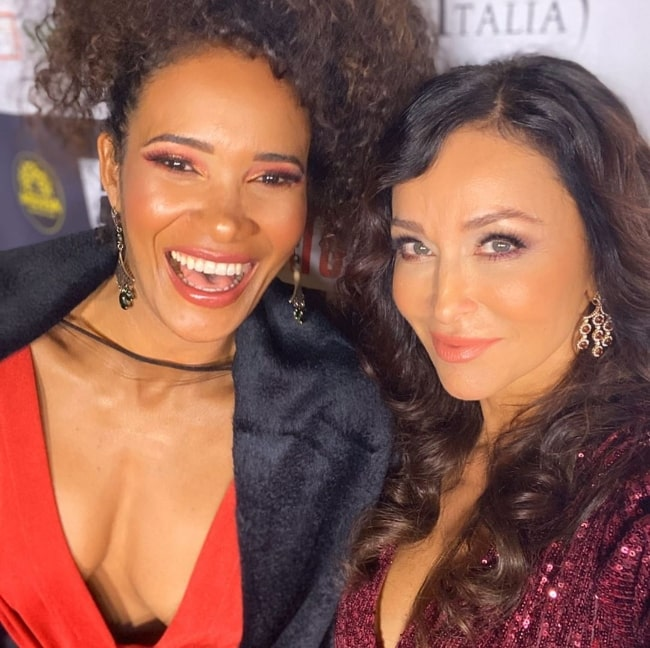 Sofia Milos (Right) smiling in a selfie alongside Denny Mendez at TCL Chinese Theatre in Los Angeles, California in February 2020