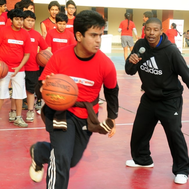 Former NBA player Muggsy Bogues, right, coaches students from the Mahindra NBA challenge youth league