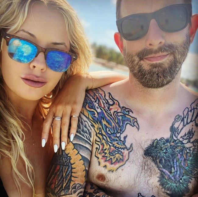 Geoff Ramsey posing shirtless alongside Emily Hatfield in December 2019