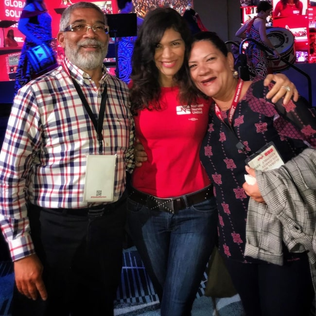 Laura Gómez posing for a picture alongside her parents