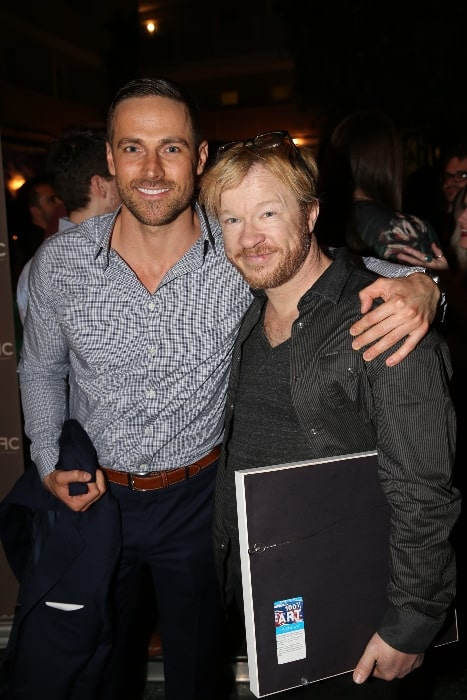 Dylan Bruce (Left) as seen while posing for the camera alongside John Fawcett at the CFC event in Los Angeles, California in May 2015