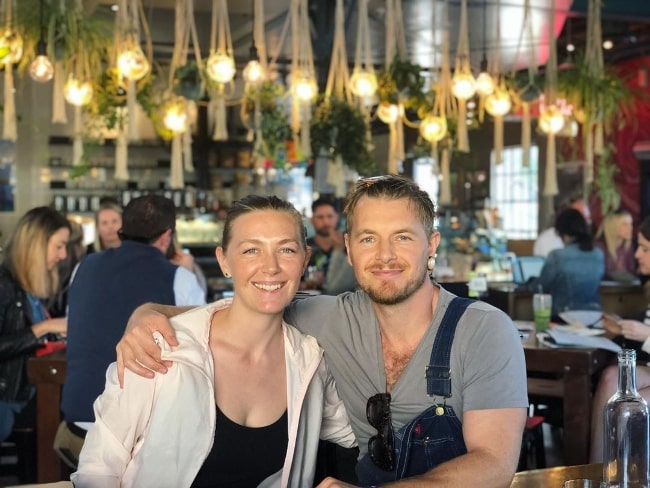 Rick Cosnett as seen while smiling for a picture alongside Michelle Alexandra at The Rose Venice in February 2020