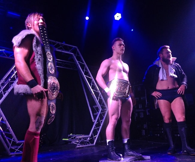 Tyler Bate (Center) as seen while holding the WWE United Kingdom Championship belt and standing on the Progress Tag Team Championship shield in January 2017