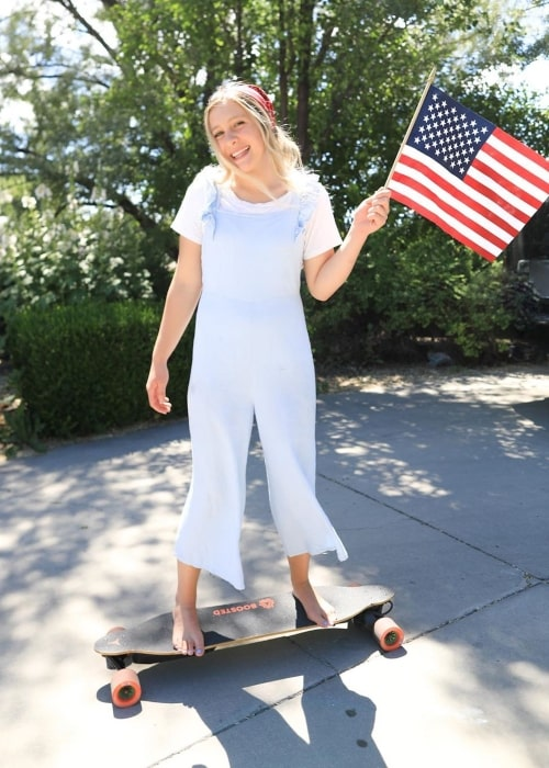 Taylor Shumway as seen in a picture taken while standing on a skateboard with the US flag in her hand and celebrating the 4th of July in the year 2020