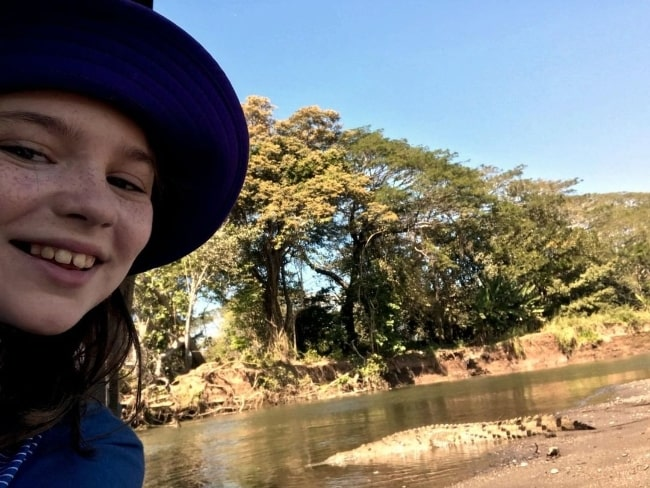 Alexa Swinton as seen while taking a selfie with a crocodile in the background in September 2019