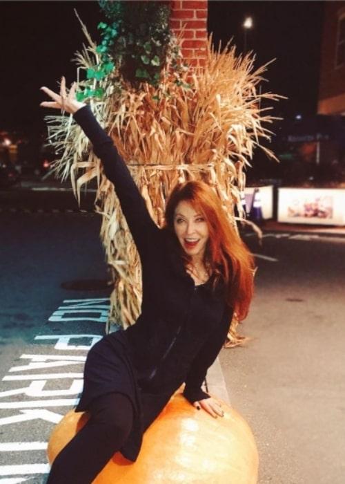 Cassandra Peterson having fun sitting on a pumpkin in November 2019